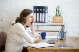 A woman sitting on her desk and yawning