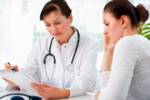 A doctor looking at the reports of female patient  who is sitting beside her stressed