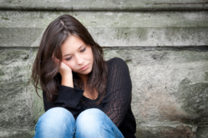Woman sitting holding her head depressed