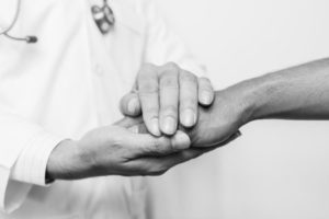 A doctor holding hand of patient to calm him