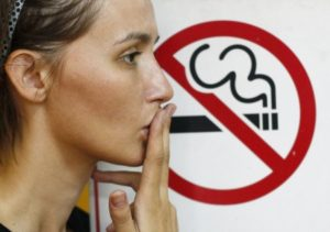 A woman doing a smoking action in front of a no-smoking sign